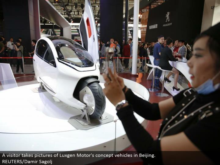 A guest takes pictures of Luxgen Motor's idea vehicles in Beijing. REUTERS/Damir Sagolj