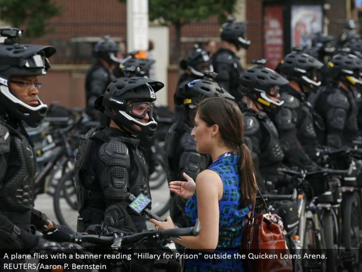 """A columnist converses with police wearing strategic rigging as they square a downtown road amid a walk by different gatherings, including """"Dark Lives Matter"""" and """"Close Down Trump and the RNC"""". REUTERS/Lucas Jackson"""
