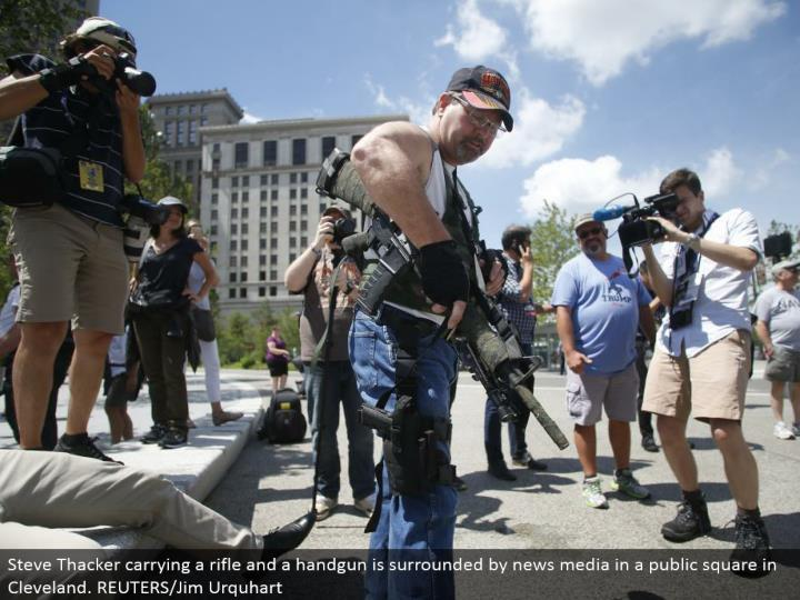 Steve Thacker conveying a rifle and a handgun is encompassed by news media in an open square in Cleveland. REUTERS/Jim Urquhart