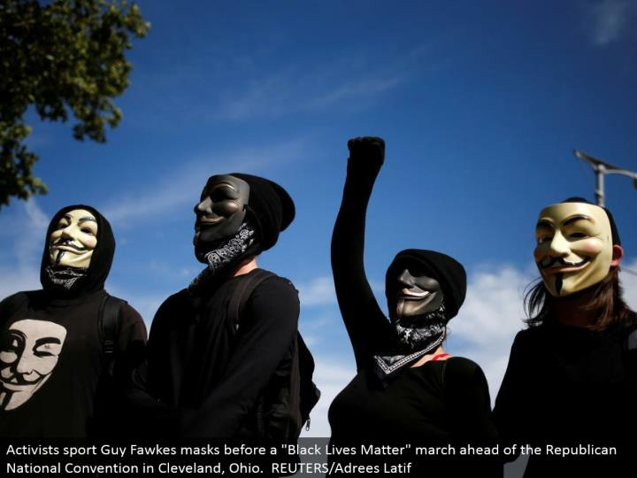 """Activists sport Guy Fawkes covers before a """"Dark Lives Matter"""" walk in front of the Republican National Convention in Cleveland, Ohio. REUTERS/Adrees Latif"""