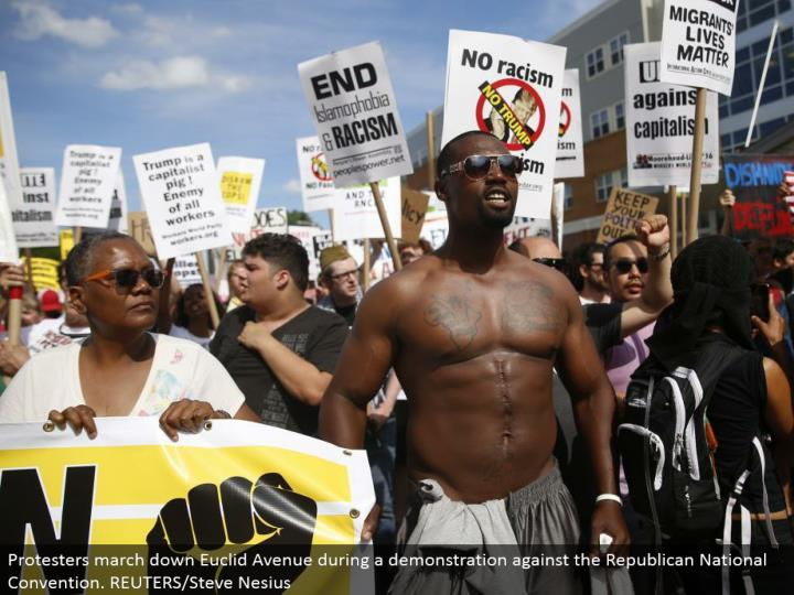 """Demonstrators hold notices amid a walk by different gatherings, including """"Dark Lives Matter"""" and """"Close Down Trump and the RNC"""". REUTERS/Shannon Stapleton"""