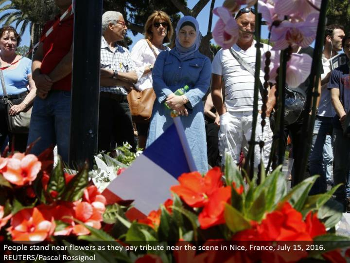 People stand close blossoms as they pay tribute close to the scene in Nice, France, July 15, 2016. REUTERS/Pascal Rossignol
