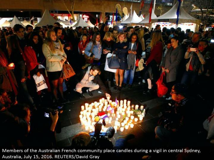Members of the Australian French people group place candles amid a vigil in focal Sydney, Australia, July 15, 2016. REUTERS/David Gray
