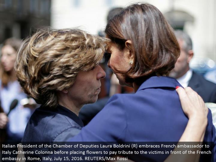 Italian President of the Chamber of Deputies Laura Boldrini (R) grasps French minister to Italy Catherine Colonna before putting blossoms to pay tribute to the casualties before the French international safe haven in Rome, Italy, July 15, 2016. REUTERS/Max Rossi