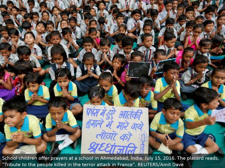 "School youngsters offer petitions at a school in Ahmedabad, India, July 15, 2016. The notice peruses, ""Tribute to the general population murdered in the dread assault in France"". REUTERS/Amit Dave"