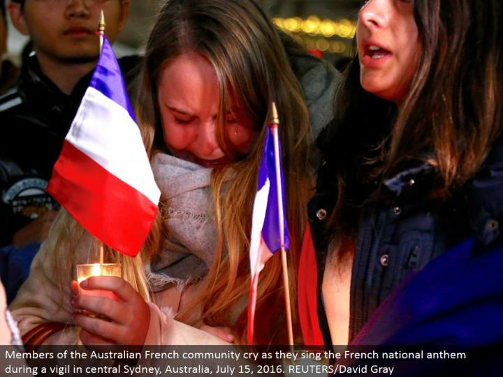 Members of the Australian French people group cry as they sing the French national song of devotion amid a vigil in focal Sydney, Australia, July 15, 2016. REUTERS/David Gray