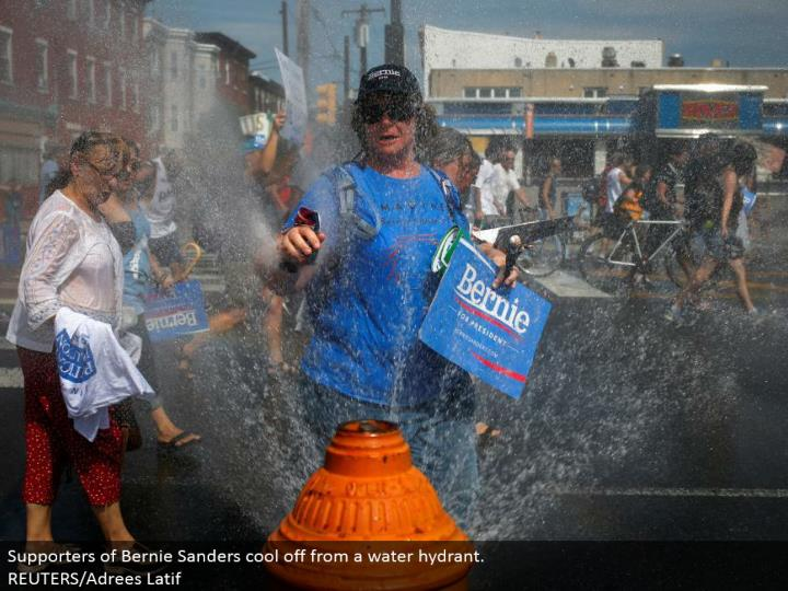 Supporters of Bernie Sanders cool off from a water hydrant.  REUTERS/Adrees Latif