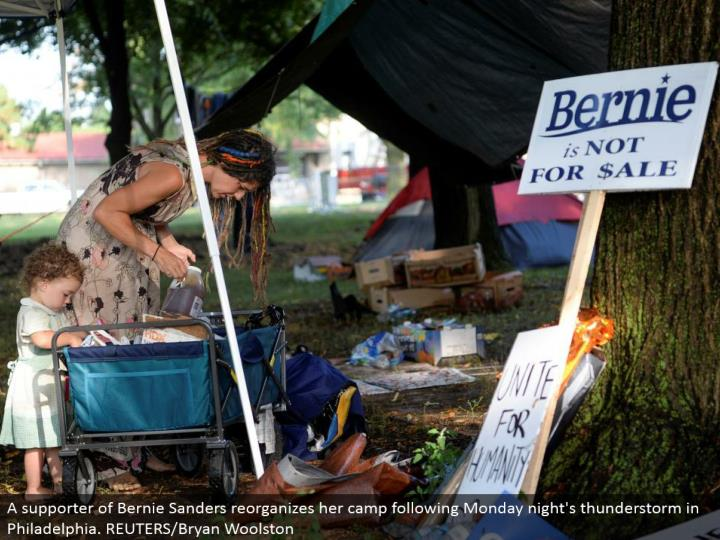 A supporter of Bernie Sanders redesigns her camp after Monday night's electrical storm in Philadelphia. REUTERS/Bryan Woolston