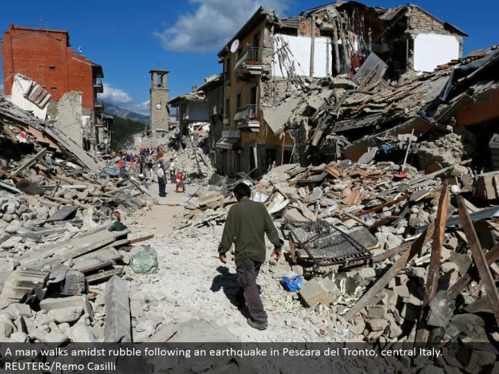 A man walks around the middle of rubble taking after a seismic tremor in Pescara del Tronto, central Italy. REUTERS/Remo Casilli