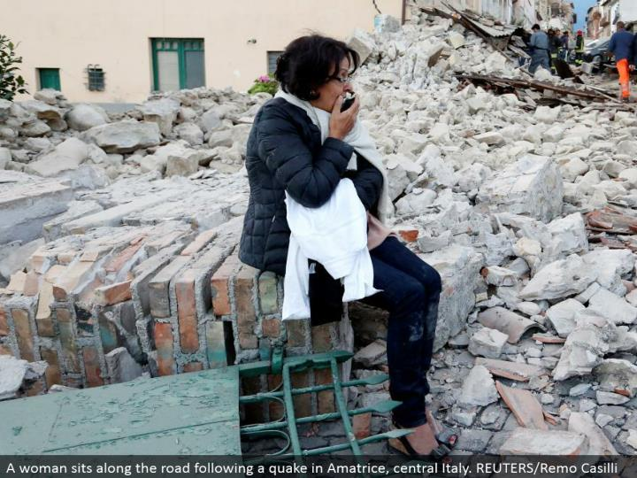 A woman sits along the road taking after a shiver in Amatrice, central Italy. REUTERS/Remo Casilli
