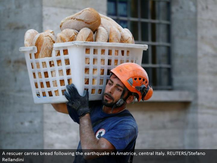 A rescuer passes on bread taking after the seismic tremor in Amatrice, central Italy. REUTERS/Stefano Rellandini