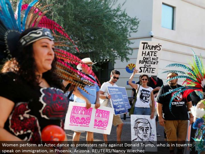 Women play out an Aztec move as dissidents rally against Donald Trump, who is around the local area to talk on migration, in Phoenix, Arizona. REUTERS/Nancy Wiechec