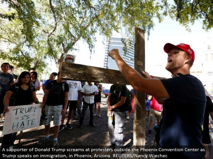 A supporter of Donald Trump shouts at dissenters outside the Phoenix Convention Center as Trump talks on migration, in Phoenix, Arizona. REUTERS/Nancy Wiechec