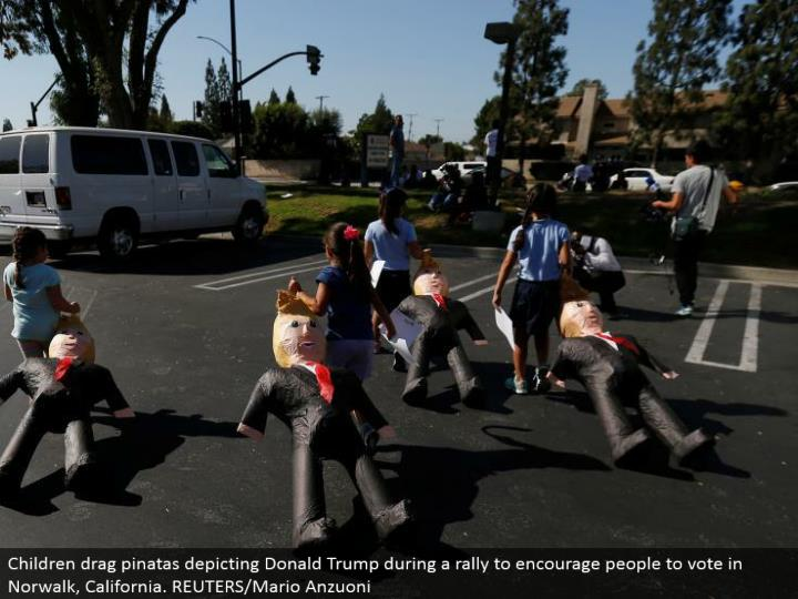 Children drag pinatas portraying Donald Trump amid a rally to urge individuals to vote in Norwalk, California. REUTERS/Mario Anzuoni