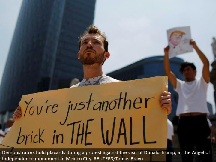 Demonstrators hold bulletins amid a dissent against the visit of Donald Trump, at the Angel of Indep...