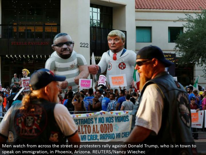 Men watch from over the road as nonconformists rally against Donald Trump, who is around the local area to talk on movement, in Phoenix, Arizona. REUTERS/Nancy Wiechec