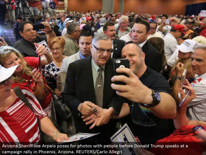 Arizona Sheriff Joe Arpaio postures for photographs with individuals before Donald Trump talks at a battle rally in Phoenix, Arizona. REUTERS/Carlo Allegri