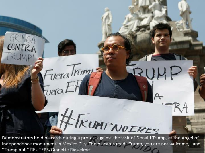 "Demonstrators hold notices amid a dissent against the visit of Donald Trump, at the Angel of Independence landmark in Mexico City. The bulletins read ""Trump, you are not welcome,"" and ""Trump out."" REUTERS/Ginnette Riquelme"