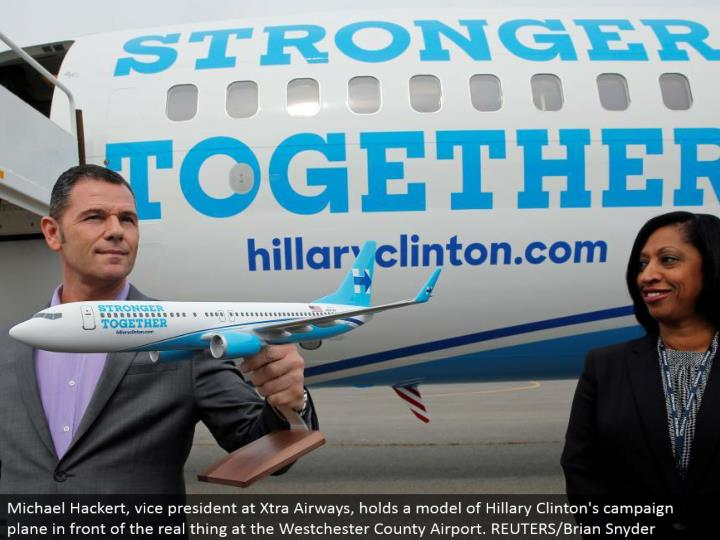 Michael Hackert, VP at Xtra Airways, holds a model of Hillary Clinton's crusade plane before the genuine article at the Westchester County Airport. REUTERS/Brian Snyder