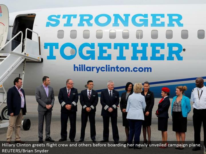 Hillary Clinton welcomes flight group and others before loading up her recently revealed battle plane. REUTERS/Brian Snyder