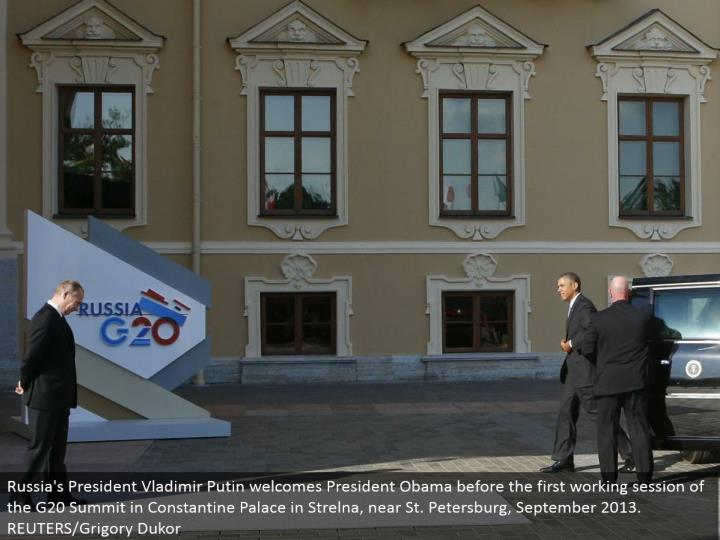 Russia's President Vladimir Putin invites President Obama before the main working session of the G20...