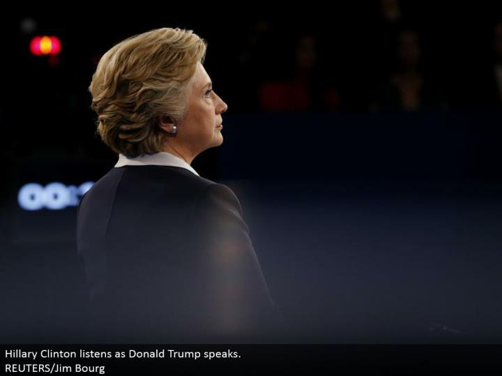 Hillary Clinton listens as Donald Trump talks.  REUTERS/Jim Bourg