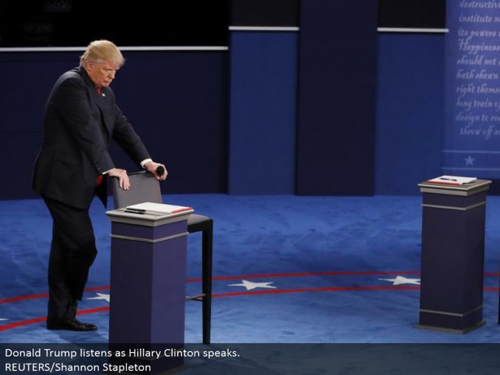 Donald Trump listens as Hillary Clinton talks.  REUTERS/Shannon Stapleton