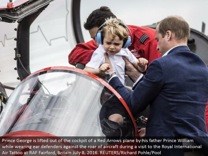 Prince George is lifted out of the cockpit of a Red Arrows plane by his dad Prince William while wearing ear guards against the thunder of flying machine amid a visit to the Royal International Air Tattoo at RAF Fairford, Britain July 8, 2016. REUTERS/Richard Pohle/Pool