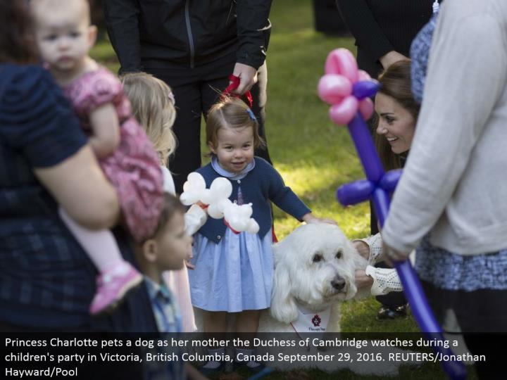 Princess Charlotte pets a puppy as her mom the Duchess of Cambridge watches amid a youngsters' gathering in Victoria, British Columbia, Canada September 29, 2016. REUTERS/Jonathan Hayward/Pool