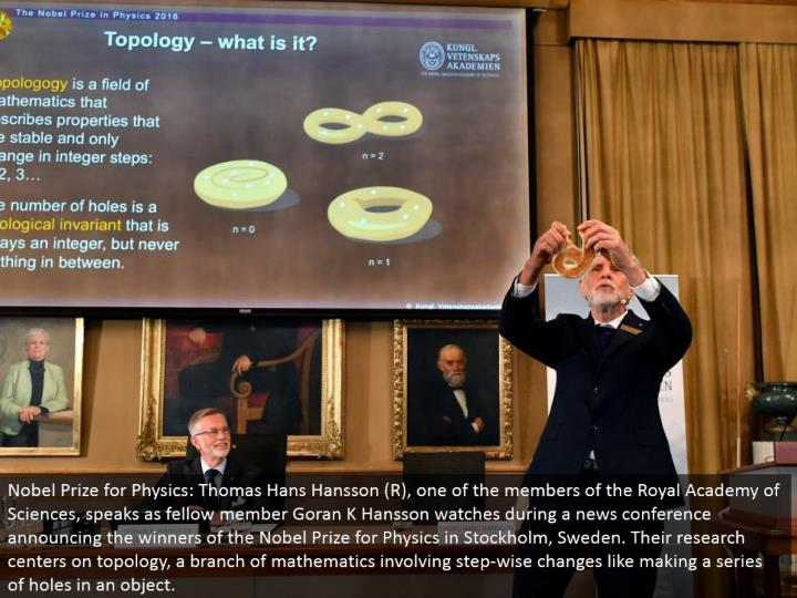 Nobel Prize for Physics: Thomas Hans Hansson (R), one of the individuals from the Royal Academy of Sciences, talks as kindred part Goran K Hansson watches amid a news gathering reporting the victors of the Nobel Prize for Physics in Stockholm, Sweden. Their exploration focuses on topology, a branch of arithmetic including step-wise changes like making a progression of openings in an object.