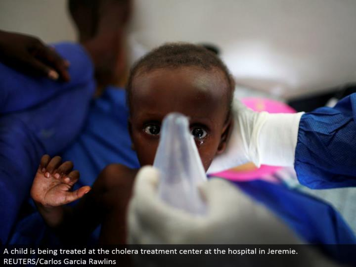 A kid is being dealt with at the cholera treatment focus at the healing facility in Jeremie. REUTERS/Carlos Garcia Rawlins