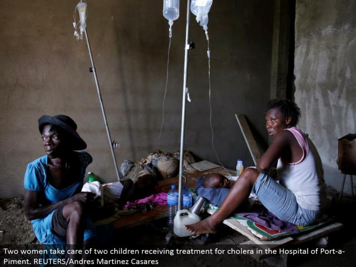 Two ladies deal with two youngsters accepting treatment for cholera in the Hospital of Port-a-Piment. REUTERS/Andres Martinez Casares