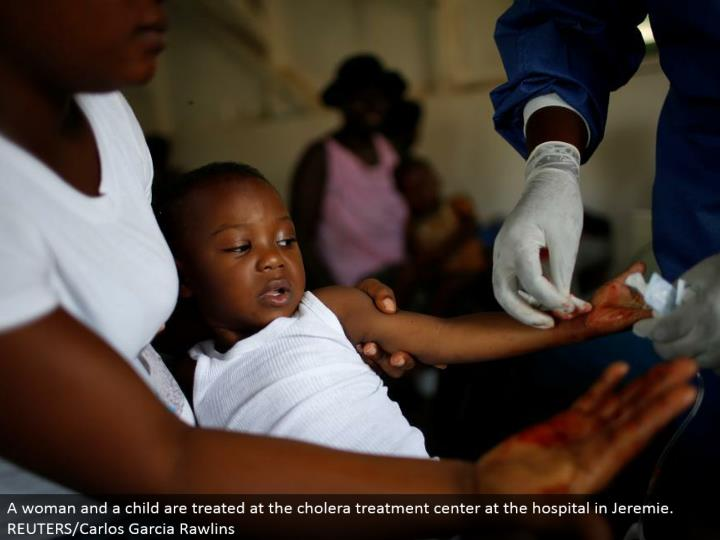 A lady and a kid are dealt with at the cholera treatment focus at the healing center in Jeremie. REUTERS/Carlos Garcia Rawlins