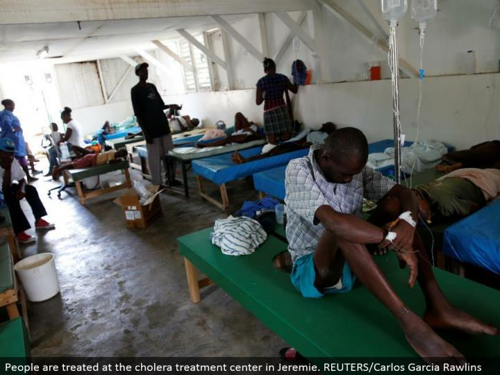 People are dealt with at the cholera treatment focus in Jeremie. REUTERS/Carlos Garcia Rawlins