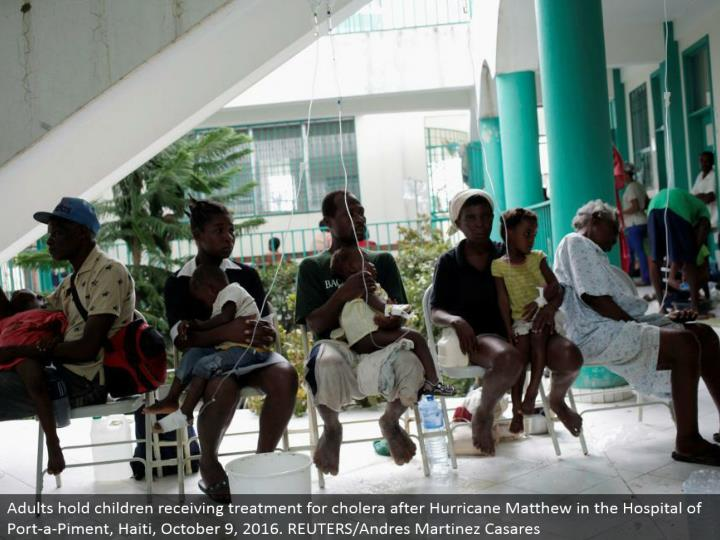 Adults hold youngsters accepting treatment for cholera after Hurricane Matthew in the Hospital of Port-a-Piment, Haiti, October 9, 2016. REUTERS/Andres Martinez Casares