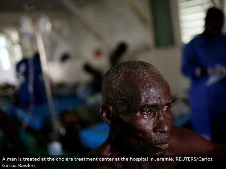 A man is dealt with at the cholera treatment focus at the healing center in Jeremie. REUTERS/Carlos Garcia Rawlins