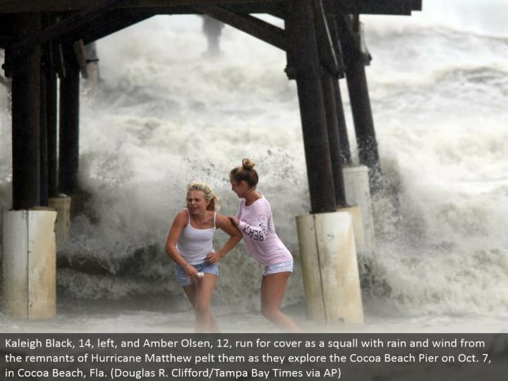 Kaleigh Black, 14, left, and Amber Olsen, 12, keep running for cover as a squall with rain and twist from the remainders of Hurricane Matthew pelt them as they investigate the Cocoa Beach Pier on Oct. 7, in Cocoa Beach, Fla. (Douglas R. Clifford/Tampa Bay Times through AP)