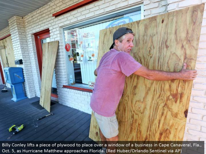 Billy Conley lifts a bit of plywood to put over a window of a business in Cape Canaveral, Fla., Oct. 5, as Hurricane Matthew approaches Florida. (Red Huber/Orlando Sentinel through AP)