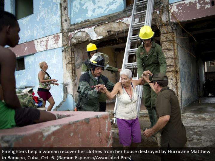 Firefighters help a lady recoup her garments from her home crushed by Hurricane Matthew in Baracoa, Cuba, Oct. 6. (Ramon Espinosa/Associated Pres)
