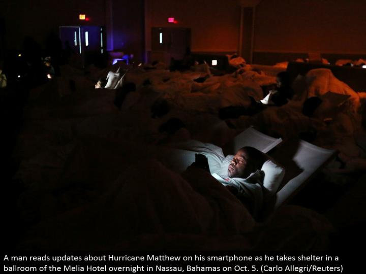 A man peruses upgrades about Hurricane Matthew on his cell phone as he takes shield in an assembly hall of the Melia Hotel overnight in Nassau, Bahamas on Oct. 5. (Carlo Allegri/Reuters)