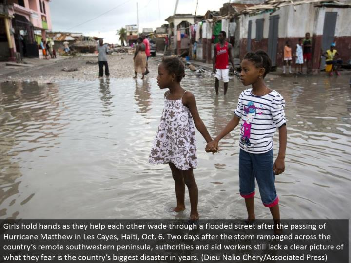 Girls clasp hands as they help each other swim through an overflowed road after the death of Hurricane Matthew in Les Cayes, Haiti, Oct. 6. Two days after the tempest rampaged the nation over remote southwestern landmass, powers and help specialists still do not have an unmistakable picture of what they dread is the nation's greatest fiasco in years. (Dieu Nalio Chery/Associated Press)