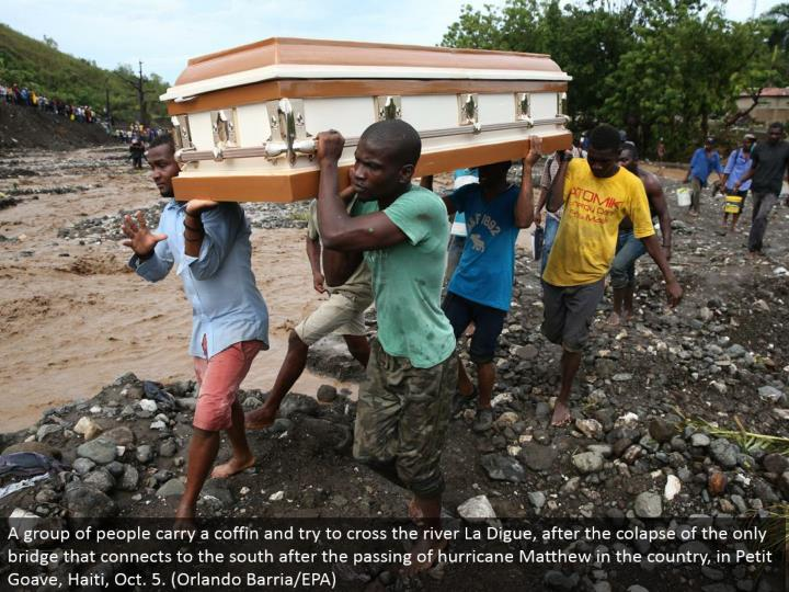 A gathering of individuals convey a casket and attempt to cross the stream La Digue, after the colapse of the main extension that interfaces with the south after the death of storm Matthew in the nation, in Petit Goave, Haiti, Oct. 5. (Orlando Barria/EPA)