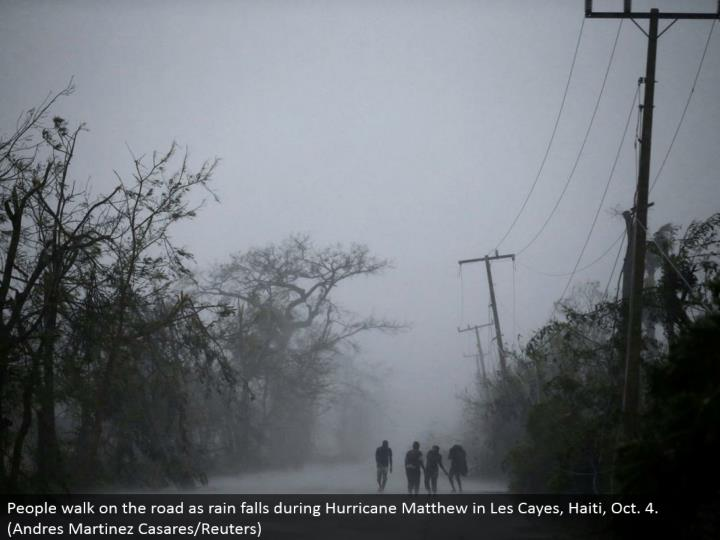 People stroll out and about as rain falls amid Hurricane Matthew in Les Cayes, Haiti, Oct. 4. (Andres Martinez Casares/Reuters)