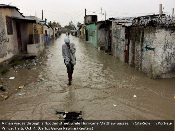A man swims through an overwhelmed road while Hurricane Matthew goes, in Cite-Soleil in Port-au-Prince, Haiti, Oct. 4. (Carlos Garcia Rawlins/Reuters)
