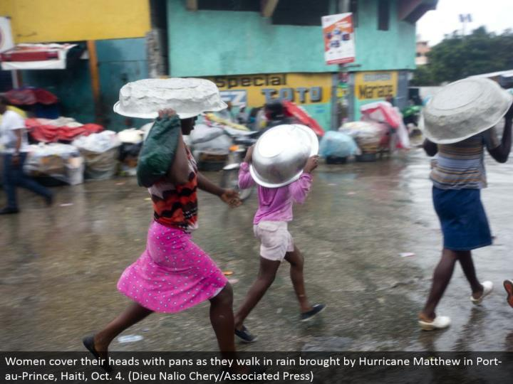 Women cover their heads with dish as they stroll in rain acquired by Hurricane Matthew Port-au-Prince, Haiti, Oct. 4. (Dieu Nalio Chery/Associated Press)