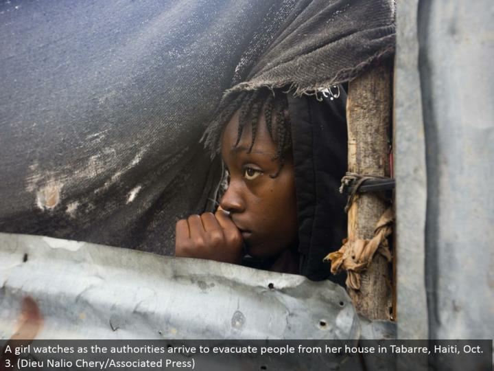 A young lady looks as the powers touch base to empty individuals from her home in Tabarre, Haiti, Oct. 3. (Dieu Nalio Chery/Associated Press)