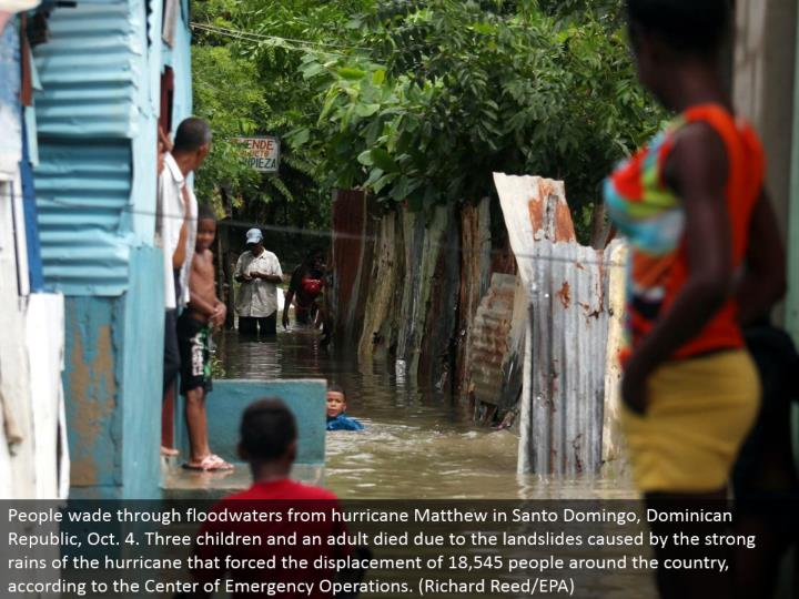 People swim through floodwaters from storm Matthew in Santo Domingo, Dominican Republic, Oct. 4. Three kids and a grown-up kicked the bucket because of the avalanches brought on by the solid downpours of the tropical storm that constrained the removal of 18,545 individuals around the nation, as indicated by the Center of Emergency Operations. (Richard Reed/EPA)