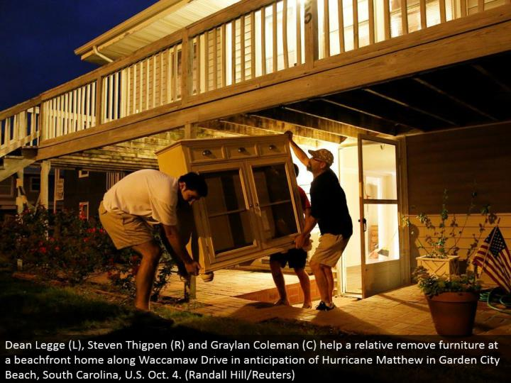Dean Legge (L), Steven Thigpen (R) and Graylan Coleman (C) help a relative evacuate furniture at a beachfront home along