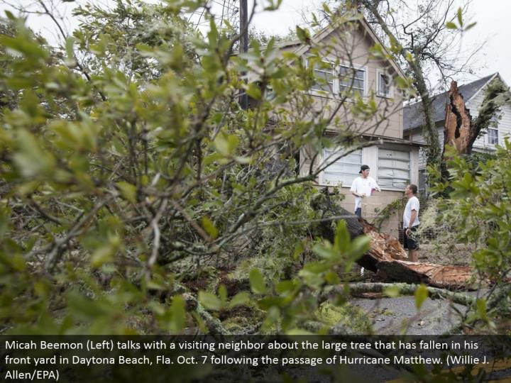 Micah Beemon (Left) converses with a meeting neighbor about the substantial tree that has fallen in his front yard in Daytona Beach, Fla. Oct. 7 taking after the section of Hurricane Matthew. (Willie J. Allen/EPA)