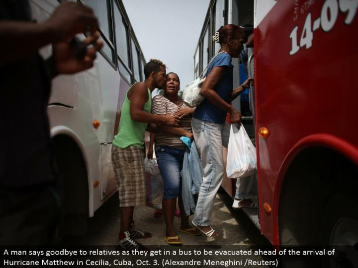 A man says goodbye to relatives as they get in a bus to be evacuated ahead of the arrival of Hurricane Matthew in Cecilia, Cuba, Oct. 3. (Alexandre Meneghini /Reuters)